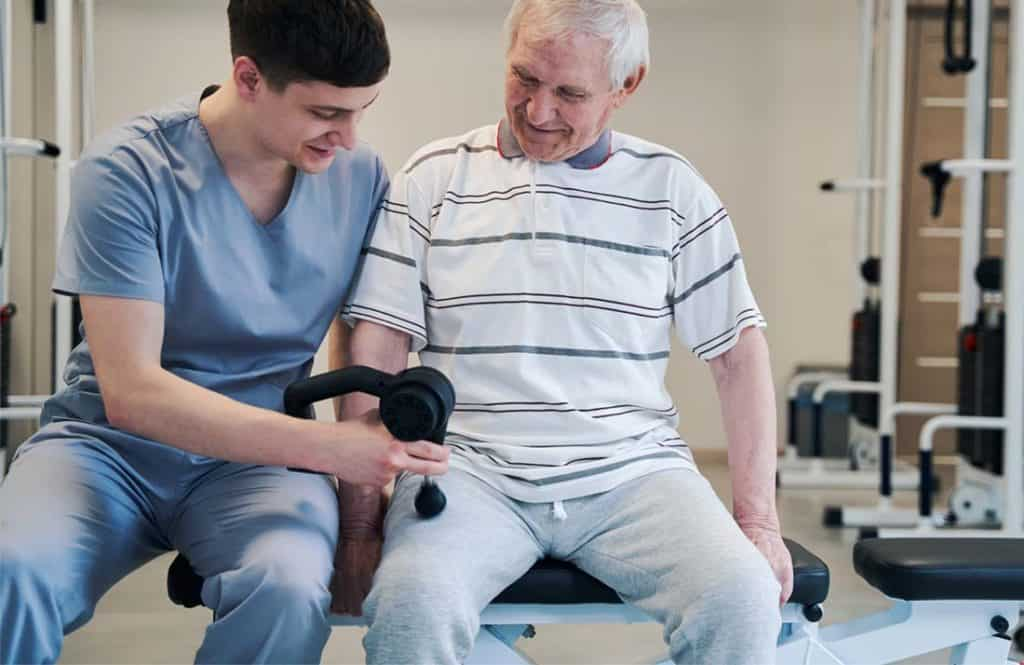 physiotherapist providing leg treatment to senior